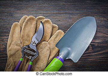 Hand spade pruning shears safety gloves on wooden board...