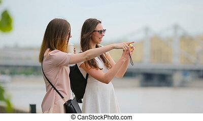 Young positive sisters having fun and making selfie Concept...