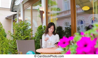 Young girl with cup of coffee using smart phone taking...