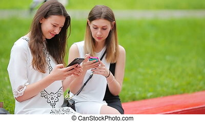 Two young girls using smart phone outdoors Two women sitting...