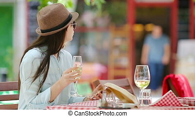 Young girl with glass of white wine using smart phone at the...