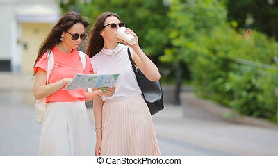 Happy young women with map walking along city street in...