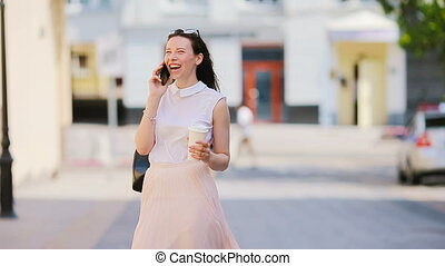 Young caucasian girl talking by her smartphone outdoor at european city.