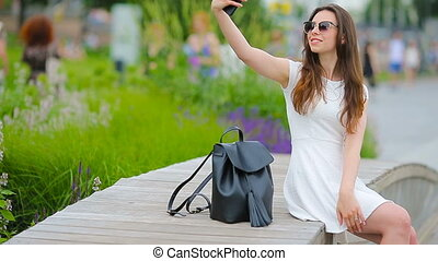 Young woman taking self portrait in european city. Caucasian...