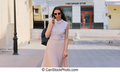 Young caucasian girl talking by her smartphone outdoor at european city. Beautiful girl in sunglasses on the street using smartphone and talking by phone with her friend