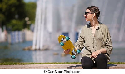 Young girl having fun with skateboard in the park. Lifestyle portrait of young positive woman having fun and enjoy warm weather.