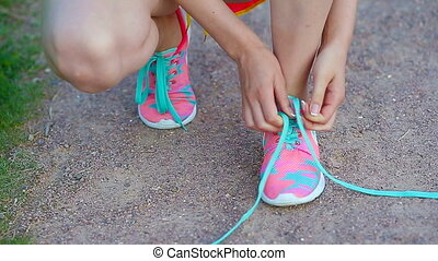 Hands of a young woman lacing bright pink and blue sneakers....