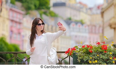 Young woman taking self portrait in european city Caucasian...