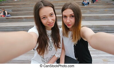 Lifestyle selfie portrait of two young positive woman having...