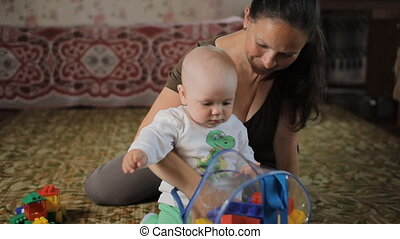 Beautiful baby playing with toys with his mother at home. The boy is less than a year