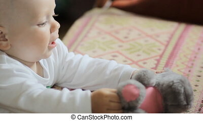The kid plays with a teddy bear at home. Handsome boy less than a year