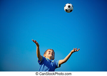 Happy boy playing ball, cute little child catching ball over...