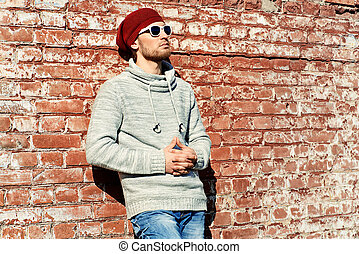 man outdoor - Handsome young man leaning against the brick...