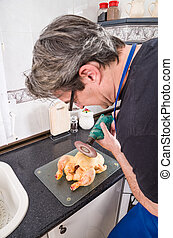 Wrong tool - Guy trying to chop a chicken with a grinder...