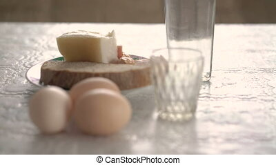 Raw eggs, bacon and bread and vodka on the table 4k
