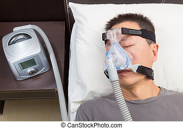 Asian man with sleep apnea using CPAP machine