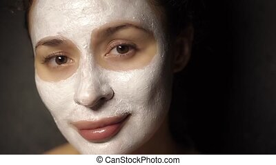 Beautiful young girl with a face pack on her face looking at...