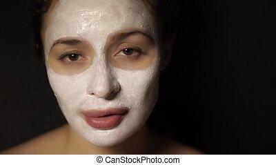 Beautiful young woman with a face pack on her face looking...