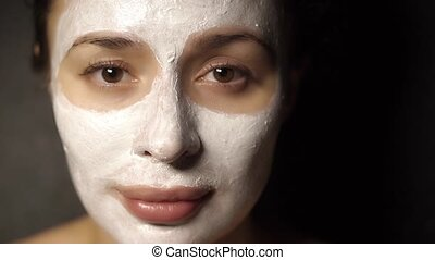 Young girl with a face pack on her face looking at the...