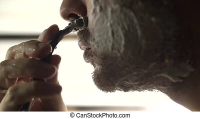 Man shaving his foamed face, close up video