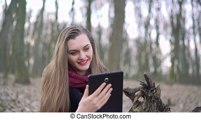 Close-up face of a girl who uses a tablet in the forest, 4k...