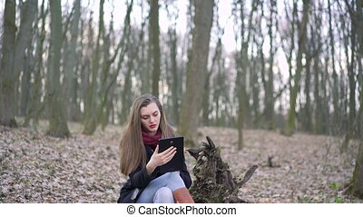 Beautiful girl sitting on a stump and using tablet. 4k -...