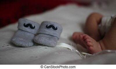 newborn feet near booties - close up of newborn feet near...