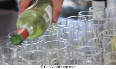 Hand of the waiter pours white wine in wineglass