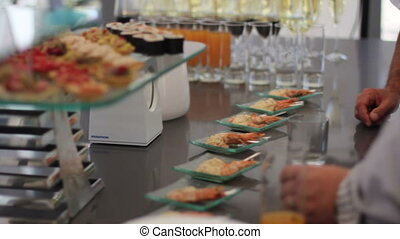 man takes canapes of shrimp from the table - Canapes of...