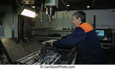 A worker removes detail from machine and check it. Machine...