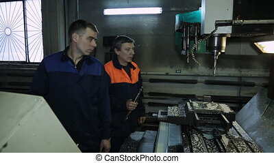 Workers change a drill bit on CNC machine. One of workers...