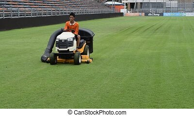 Mowing grass in a football stadium - Bangkok, Thailand -...