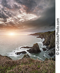 Dramatic stormy sunrise landscape over Bull Point in Devon England