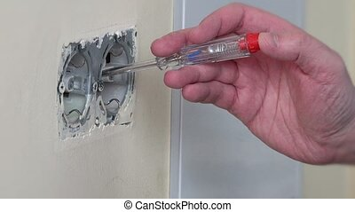 Electrician hand test power on wall socket.