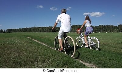 Summer field classical bicycling, slow motion steadicam shot