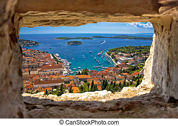 Hvar bay aerial view through stone window from Fortica...