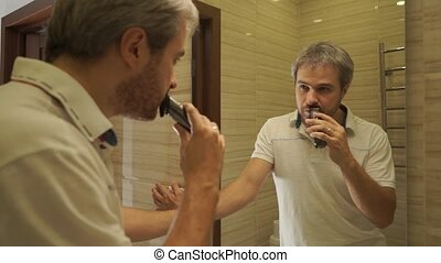 A man trimming his beard in the bathroom - Dolly shot, slow...