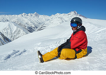 snowboarder sits high in mountains on the edge of slope -...