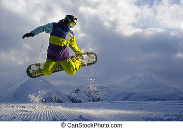 snowboarder does the jumping trick snow scatters pieces of...
