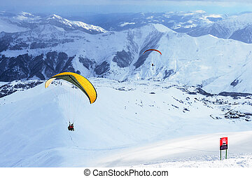 glider flying in mountainous terrain in winter