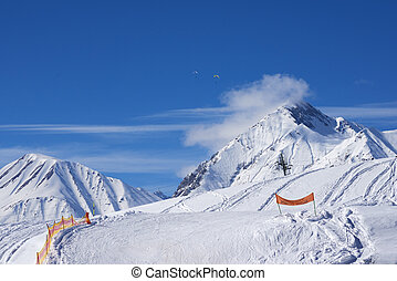 Alpine ski resort of snow-covered rocks bright winter day -...
