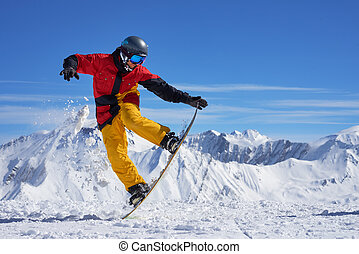 Snowboarder doing trick - Snowboarder in bright sportswear...