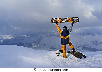 Snowboarder raised board above his head standing on a cliff...