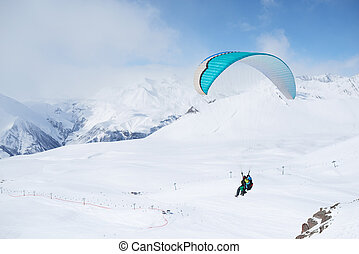 paragliding daytime in the mountainous areas in winter On...