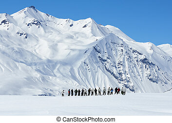 large group of people from afar in mountains in winter -...