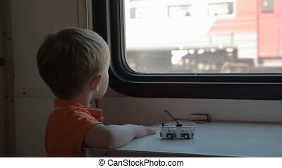 Boy looking out the train window - Little boy looking...