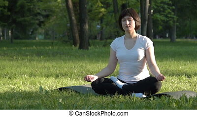 Girl doing yoga in the park at sunset - Young woman...