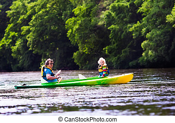 Father and child kayaking in summer