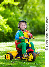 Little boy on colorful tricycle - Cute boy wearing safety...