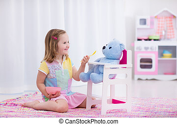 Little girl feeding her toy bear - Little cute girl playing...